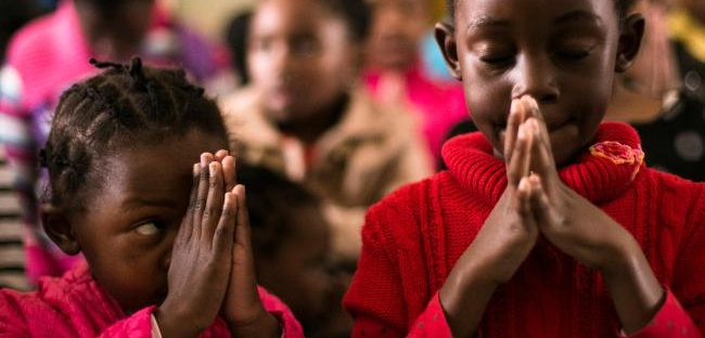 Children pray during a Sunday school following a mass in which a priest spoke about former South African President Nelson Mandela, at a Methodist church in Soweto township on the outskirts of  Johannesburg, South Africa, Sunday, July 7, 2013. Nelson Mandela has been in a hospital for nearly a month. (AP Photo/Markus Schreiber)