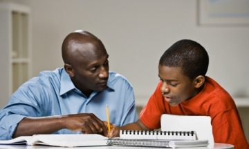 Edmonds, Washington State, USA --- African American father helping son with homework --- Image by © Andersen Ross/Blend Images/Corbis